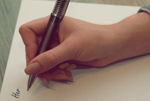 žena píše na papír poznámky