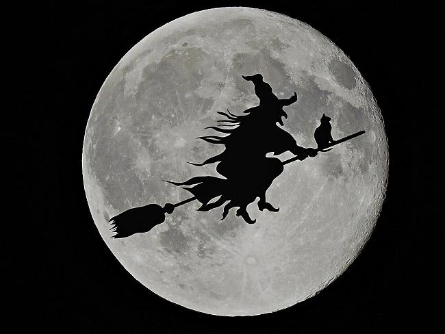 čarodějnice s kočkou letí na koštěti okolo Měsíce